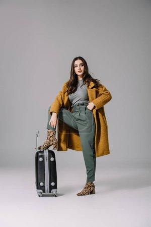 Photo pour Belle femme élégante en manteau beige posant avec sac de voyage sur gris - image libre de droit