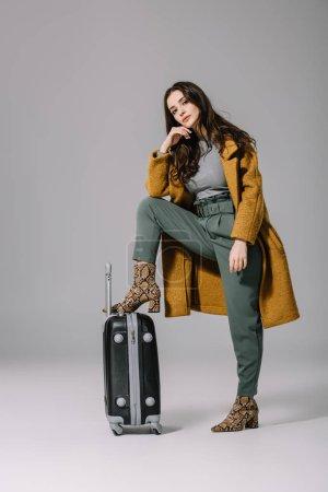 Photo pour Femme à la mode en manteau beige posant avec un sac de voyage sur gris - image libre de droit
