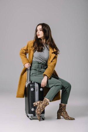Photo pour Fillette à la mode en manteau beige assise sur un sac de voyage gris - image libre de droit
