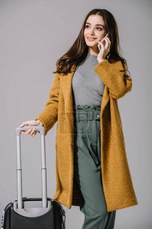 Photo pour Femme souriante en manteau beige posant avec sac de voyage et parlant sur smartphone, isolée sur gris - image libre de droit