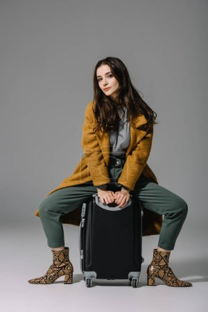 Photo for Attractive woman in beige coat sitting on travel bag on grey - Royalty Free Image