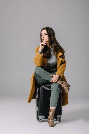 Photo pour Belle femme chère en manteau beige assise sur sac de voyage sur gris - image libre de droit
