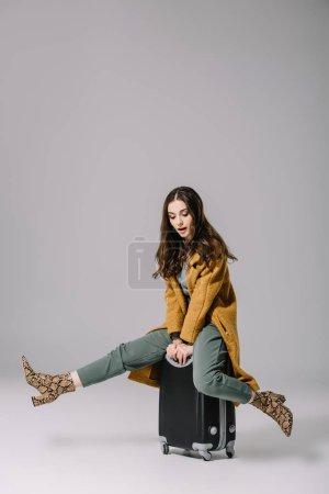 Photo pour Heureuse élégante fille élégante en manteau beige assis sur le sac de voyage sur gris - image libre de droit