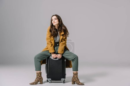 Photo for Fashionable elegant girl in beige coat sitting on travel bag on grey - Royalty Free Image