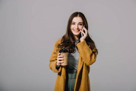 Photo pour Jolie fille souriante en manteau beige tenant un café pour aller parler sur un smartphone, isolée sur grise - image libre de droit