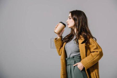 Photo pour Belle femme en manteau beige buvant du café à emporter, isolée sur gris - image libre de droit