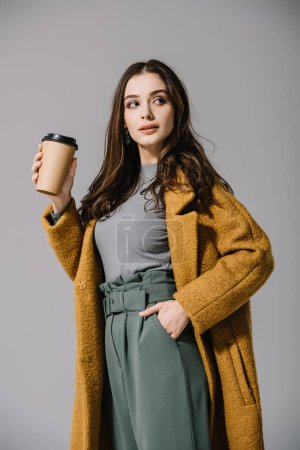 Photo pour Attractive girl in beige coat holding coffee to go, isolated on grey - image libre de droit