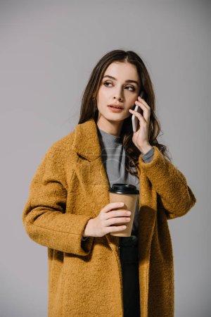 Photo pour Belle fille en manteau beige tenant un café pour aller tout en parlant sur smartphone, isolée sur gris - image libre de droit