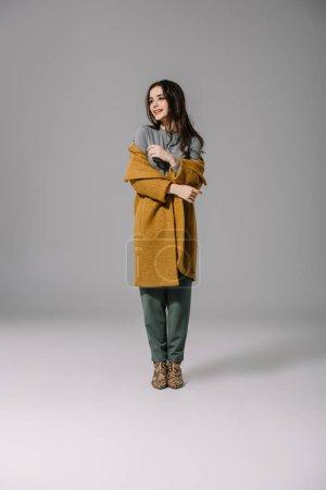 Photo pour Élégante à la mode posant en manteau beige sur gris - image libre de droit