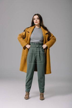 Photo pour Modèle élégant posant en manteau beige sur gris - image libre de droit