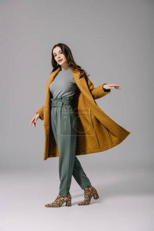 Photo pour Femme élégante posant en manteau d'automne beige sur gris - image libre de droit