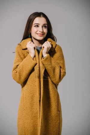 Photo pour Smiling cold girl posing in warm beige coat, isolated on grey - image libre de droit