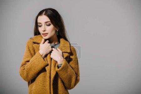 Photo pour Jolie fille froide posant en manteau beige chaud, isolé sur gris - image libre de droit