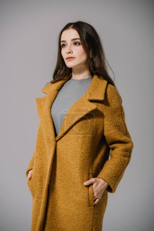 Photo for Elegant pretty woman posing in beige coat, isolated on grey - Royalty Free Image