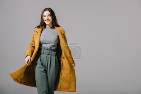Photo pour Élégante fille gaie posant en manteau beige, isolé sur gris - image libre de droit