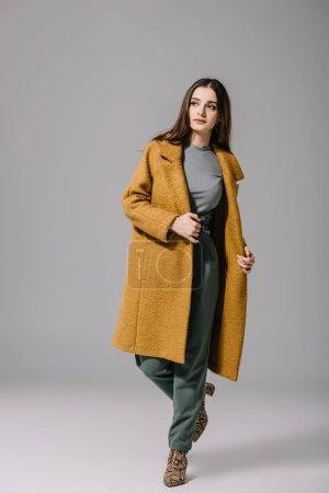 Photo pour Attrayant élégant fille posant en manteau beige sur gris - image libre de droit