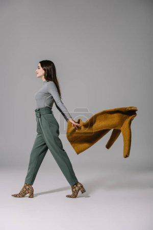 Photo pour Élégante fille élégante décoller manteau beige sur gris - image libre de droit
