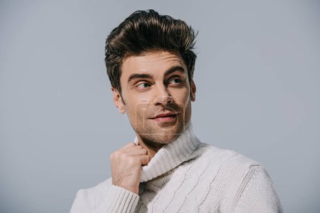Photo pour Bel homme élégant posant en pull tricoté blanc, isolé sur gris - image libre de droit