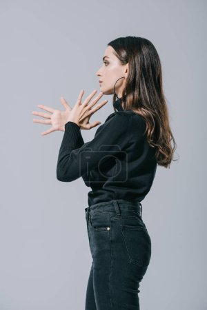 Photo pour Side view of fashionable girl gesturing and posing in black sweater, isolated on grey - image libre de droit