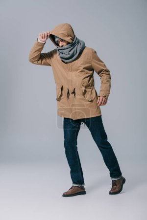 Photo pour Jeune homme à la mode posant en chapeau, écharpe et manteau sur gris - image libre de droit
