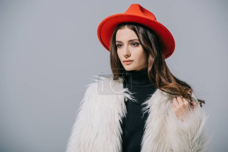 Photo pour Beautiful elegant woman posing in white fur coat and red hat, isolated on grey - image libre de droit