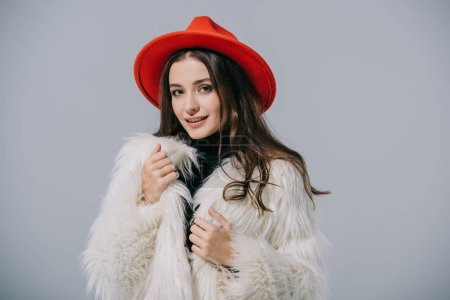 Photo pour Smiling elegant girl posing in trendy fur coat and red hat, isolated on grey - image libre de droit