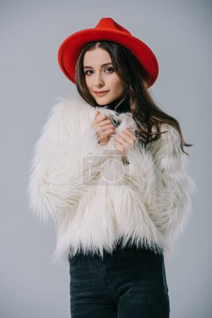 Photo pour Beautiful elegant model posing in white fur coat and red hat, isolated on grey - image libre de droit
