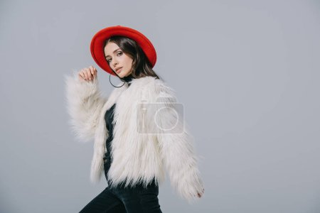 Photo pour Elegant lady posing in white fur coat and red hat, isolated on grey - image libre de droit