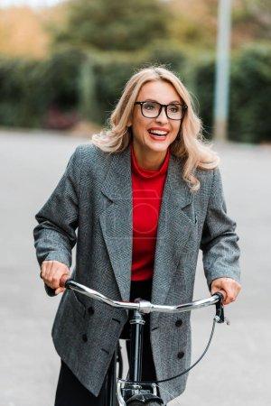 Foto de Atractiva mujer de negocios en abrigo y gafas sonriendo y montar en bicicleta - Imagen libre de derechos