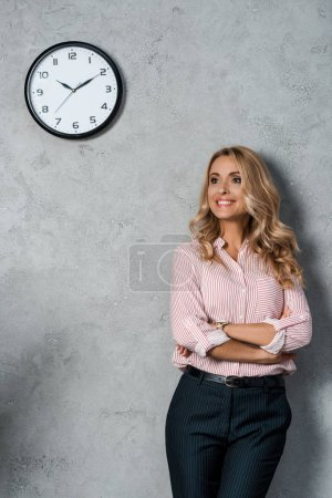Photo for Attractive businesswoman with crossed arms smiling and looking away - Royalty Free Image