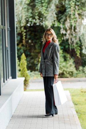 Foto de Atractiva mujer de negocios en abrigo y gafas sosteniendo bolsa de compras - Imagen libre de derechos