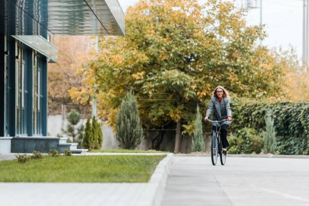 Photo for Attractive businesswoman in coat and glasses smiling and riding bike - Royalty Free Image