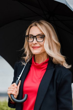 Photo for Attractive businesswoman in coat and glasses holding black umbrella - Royalty Free Image