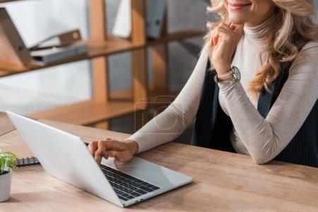 Photo pour Vue recadrée de femme d'affaires assise à table et utilisant un ordinateur portable - image libre de droit