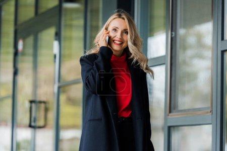 Photo pour Femme d'affaires attrayante et souriante en manteau noir parlant sur smartphone - image libre de droit