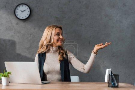 attraktive und lächelnde Geschäftsfrau, die mit der Hand zeigt und am Tisch sitzt