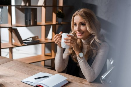 attractive and smiling businesswoman sitting at table and holding cup