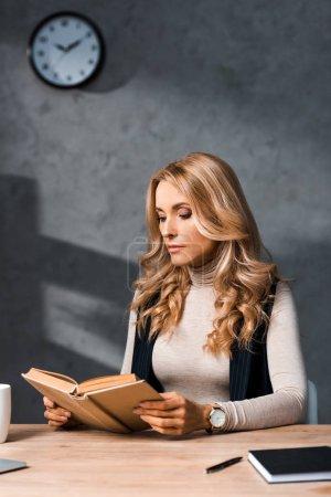 Photo pour Attrayant et blonde femme d'affaires assis à la table et le livre de lecture - image libre de droit