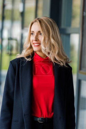 Photo for Attractive and smiling businesswoman in black coat looking away - Royalty Free Image