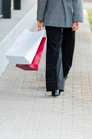 Photo pour Crochet vue d'une femme d'affaires en manteau gris tenant des sacs à provisions - image libre de droit