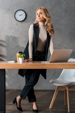 attractive and blonde businesswoman standing and looking away in office