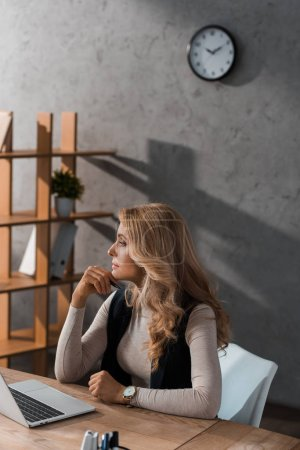 attractive and blonde businesswoman sitting at table and looking away
