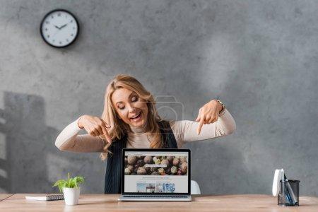 Photo pour KYIV, UKRAINE - 16 AOÛT 2019 : femme d'affaires souriante pointant des doigts vers un ordinateur portable avec le site depositphotos - image libre de droit