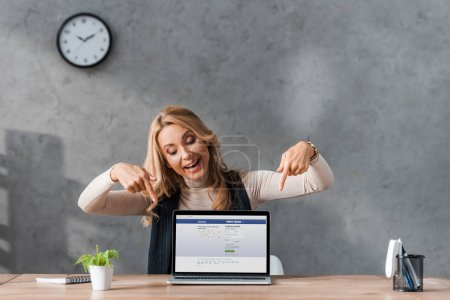 KYIV, UKRAINE - AUGUST 16, 2019: smiling businesswoman pointing with fingers at laptop facebook website