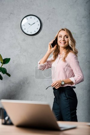 Photo for Smiling and attractive businesswoman in shirt talking on smartphone - Royalty Free Image