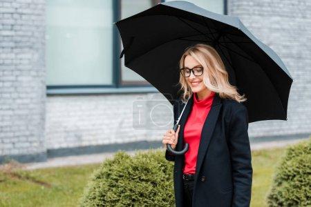 Foto de Atractiva y sonriente empresaria con abrigo negro sosteniendo paraguas - Imagen libre de derechos