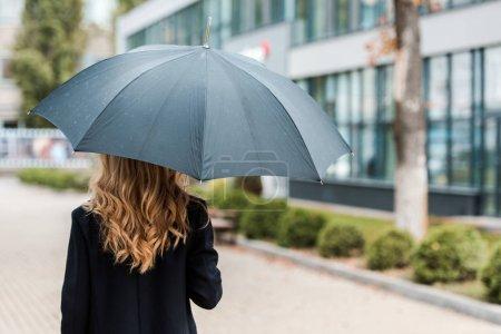 Rückansicht der blonden Geschäftsfrau im schwarzen Mantel mit Regenschirm
