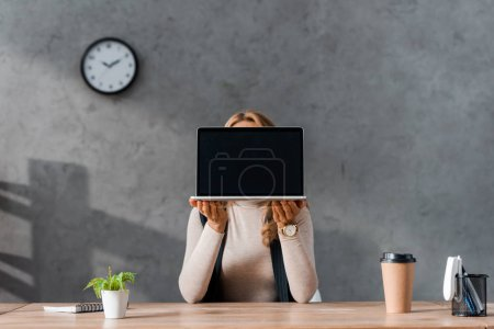 businesswoman sitting at table and holding laptop with copy space