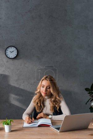 attraktive und blonde Geschäftsfrau sitzt am Tisch und schreibt in Notizbuch