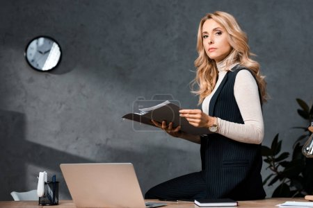 attractive and blonde businesswoman holding papers and sitting on table in office